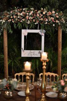 Ρουστίκ στολισμός δεξίωσης γάμου με ξύλινη αψίδα και λουλούδια