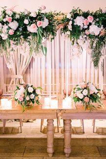 Ρομαντικός παραμυθένιος στολισμός δεξίωσης γάμου με πλούσιες ανθοσυνθέσεις και πολλά κεριά