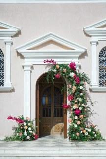 Πανεμορφος στολισμος εισοδου εκκλησιας με πλουσιες συνθεσεις λουλουδιων και πρασιναδα