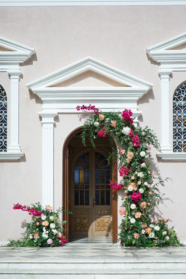 Πανέμορφος στολισμός εισόδου εκκλησίας με πλούσιες συνθέσεις λουλουδιών και πρασινάδα