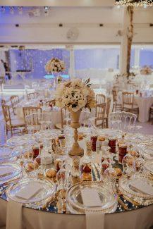Glamorous στολισμός δεξίωσης γάμου με λουλούδια σε χρυσά βάζα