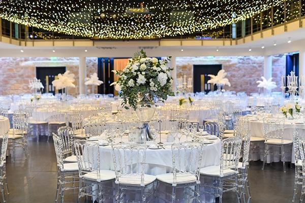 Ρομαντικός στολισμός δεξίωσης γάμου με λευκές ανθοσυνθέσεις και fairy lights