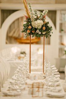 Elegant centerpieces για δεξιωση γαμου με λουλουδια και πρασιναδα σε χρυσα stands