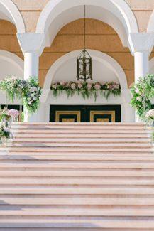 Εντυπωσιακος στολισμος εισοδου εκκλησιας με πλουσιες συνθεσεις λουλουδιων και χρυσα stands