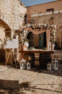 Στολισμός δεξίωσης γάμου με λουλουδένια αψίδα, υφάσματα και φαναράκια