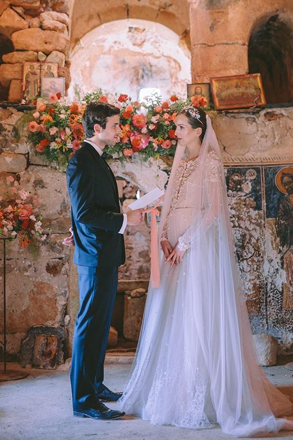 Στολισμός τελετής γάμου με πλούσιες γιρλάντες λουλουδιών σε peach αποχρώσεις