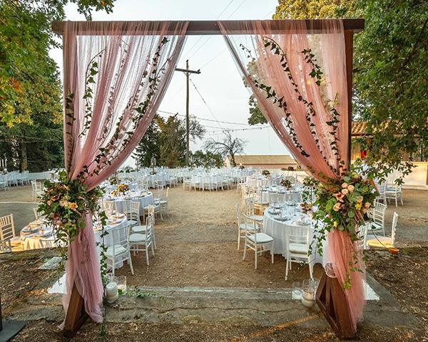 Υπεροχος στολισμος ξυλινης αψιδας για δεξιωση γαμου με υφασματα και λουλουδια