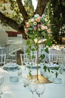 Ασυμμετρα μπουκετα λουλουδιων με κερια σε χρυσα stand για στολισμο δεξιωσης γαμου