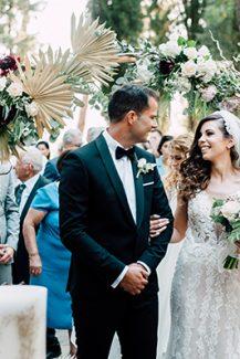 Εντυπωσιακή ξύλινη αψίδα για στολισμό δεξίωσης γάμου με αποξηραμένα φύλλα φοίνικα και μπορντό λεπτομέρειες