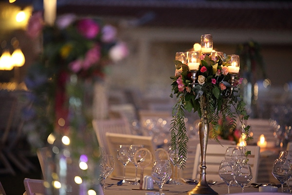 Στολισμός δεξίωσης με centerpieces από ψηλά κηροπήγια και λουλούδια