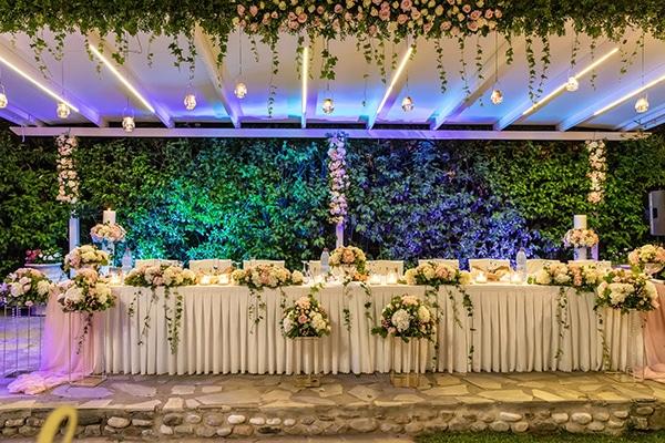 Εντυπωσιακός στολισμός τραπεζιού δεξίωσης γάμου με πλούσιες ανθοσυνθέσεις