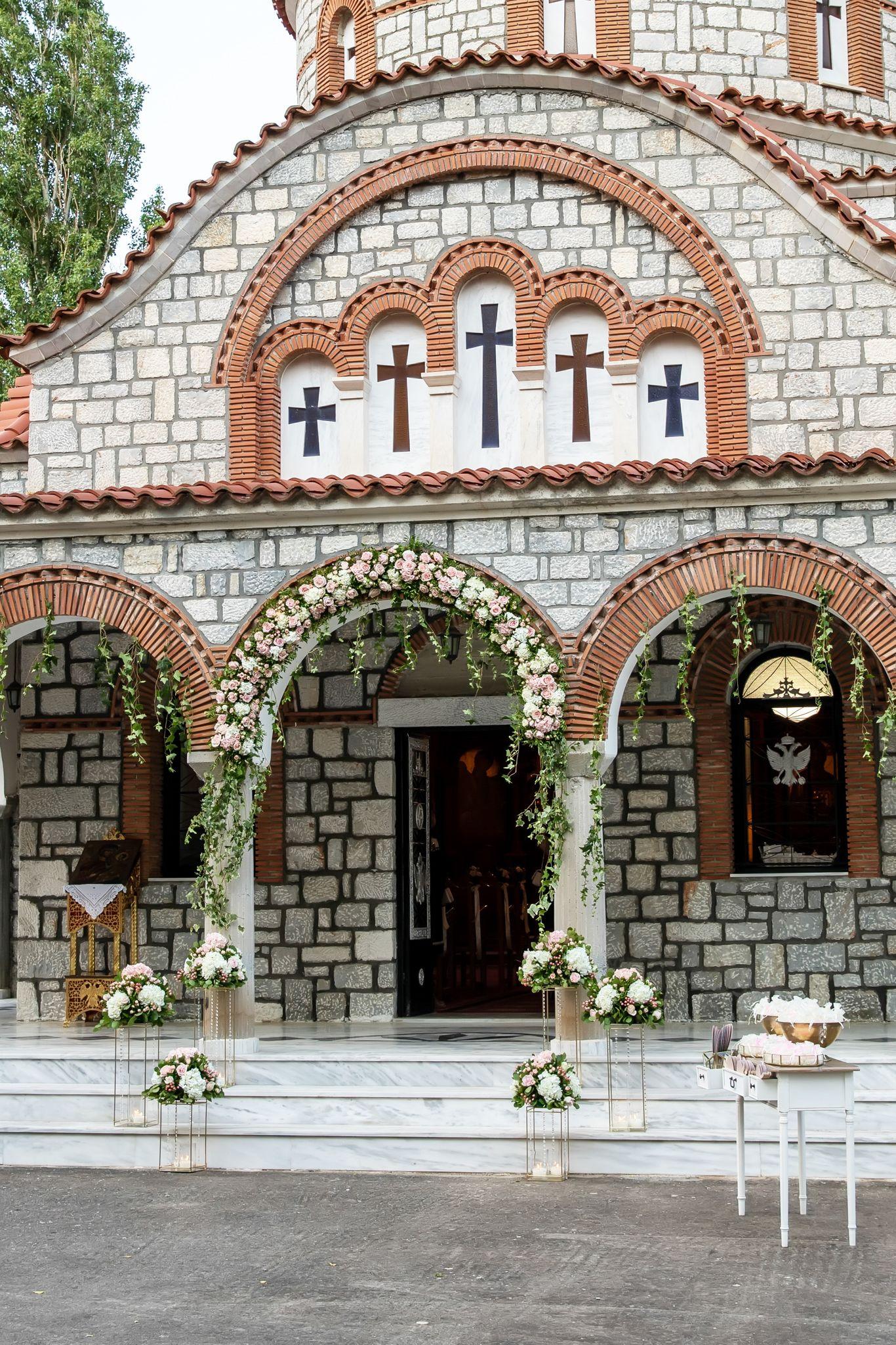 Όμορφος στολισμός εισόδου εκκλησίας με γιρλάντα λουλουδιών