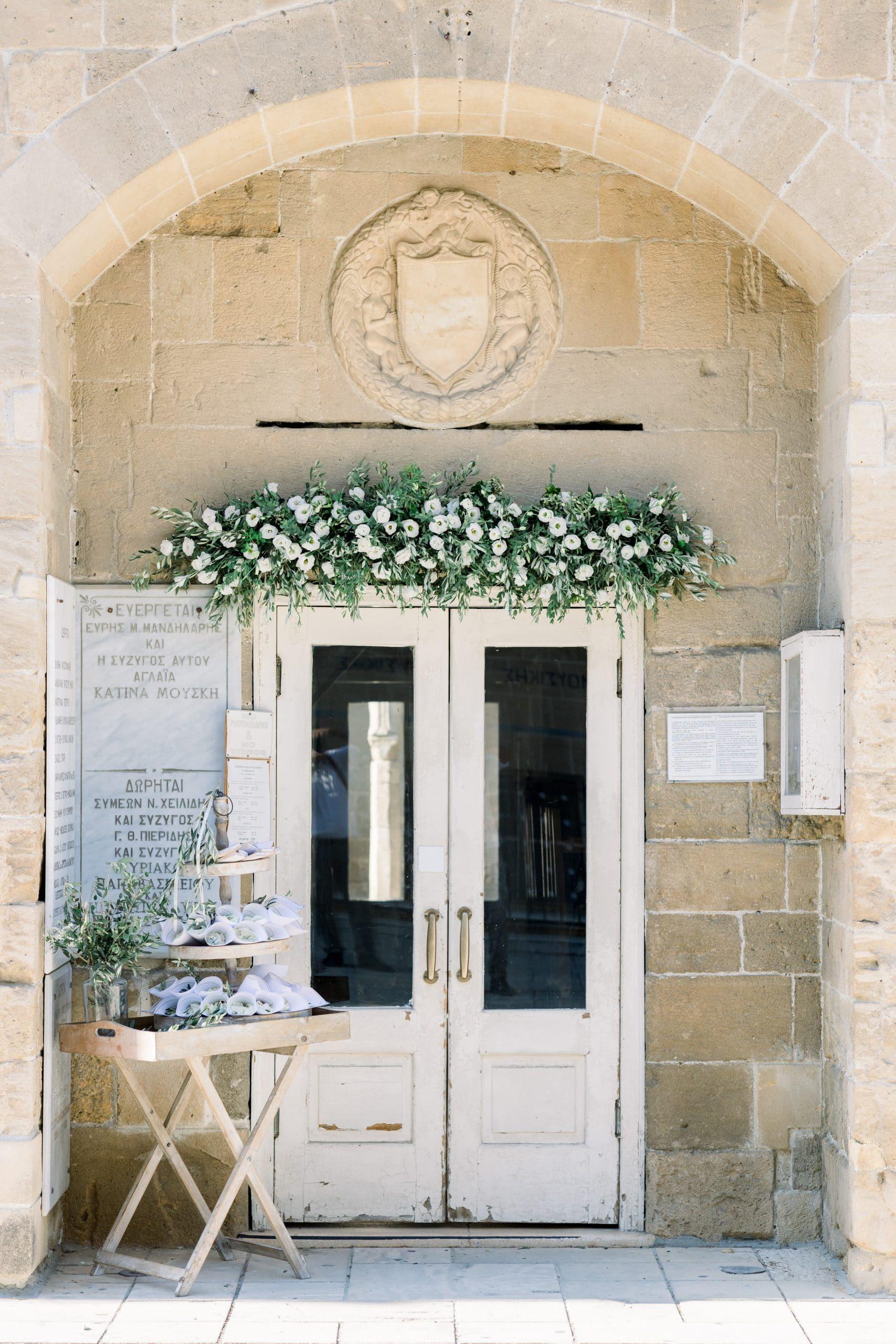 Ρομαντικός στολισμός εισόδου εκκλησίας με γιρλάντα από φρέσκα λουλούδια