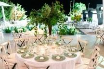 Πανεμορφος στολισμος τραπεζιων δεξιωσης γαμου με ψηλες συνθεσεις πρασιναδας