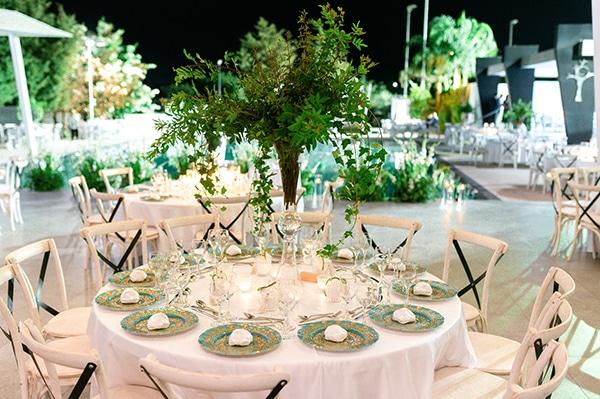 Πανέμορφος στολισμός τραπεζιών δεξίωσης γάμου με ψηλές συνθέσεις πρασινάδας