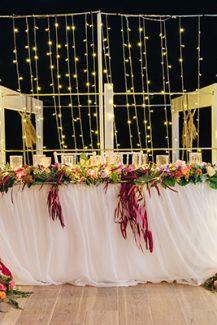 Μοντέρνος στολισμός γαμήλιου τραπεζιού με λουλούδια σε έντονες αποχρώσεις