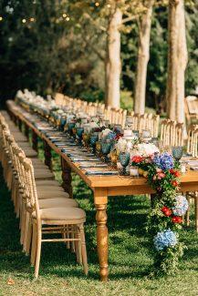Στολισμός δεξίωσης εξωτερικού χώρου με ξύλινα τραπέζια και λουλούδια