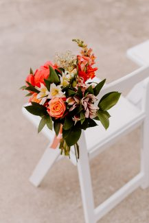 Στολισμός καρέκλας καλεσμένων με κοραλί λουλούδια