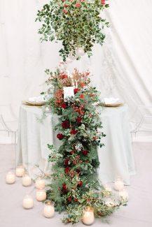 Γιορτινός στολισμός τραπεζιού δεξίωσης με γιρλάντες λουλουδιών και κεριά