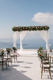Πανέμορφη αψίδα για τελετή γάμου με λουλούδια και υφάσματα
