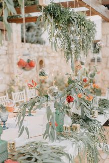 Υπέροχος στολισμός τραπεζιών δεξίωσης με ευκάλυπτο και άνθη σε γυάλινα βαζάκια