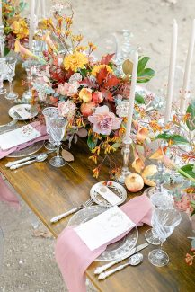 Στολισμός γαμήλιου τραπεζιού με πλούσιες ανθοσυνθέσεις από τριαντάφυλλα, ντάλιες και κρίνα σε αποχρώσεις του κίτρινου και του σάπιου μήλου