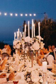 Ρομαντικός στολισμός τραπεζιού δεξίωσης με λευκά κεριά και λευκές ανθοσυνθέσεις