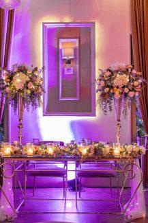 Stylish στολισμός γαμήλιου τραπεζιού με λουλούδια σε ψηλούς αμφορείς