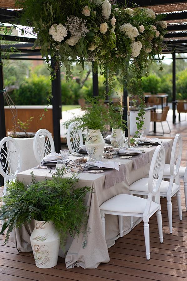 Πλούσιος ανθοστολισμός γαμήλιου τραπεζιού με ορτανσίες και τριαντάφυλλα και κρεμαστές πρασινάδες με κισσούς