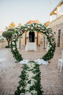Εντυπωσιακή λουλουδένια κυκλική αψίδα με λευκές ορτανσίες και ροζ τριαντάφυλλα