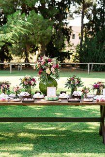 Ξύλινο candy table εμπλουτισμένο με πολύχρωμα λουλούδια