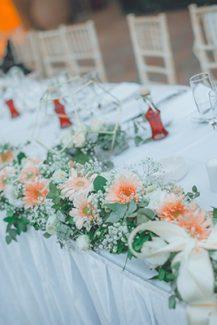Ρομαντικός στολισμός γαμήλιου τραπεζιού με ανοιξιάτικα λουλούδια σε coral αποχρώσεις