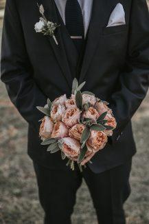 Στρογγυλή ανθοδέσμη με τριαντάφυλλα σε peach αποχρώσεις και φύλλα ευκαλύπτου