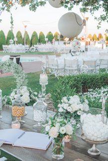 Τραπέζι ευχών διακοσμημένο με λευκά τριαντάφυλλα και γλυκήσματα