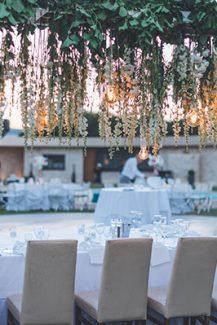 Στολισμός γαμήλιου τραπεζιού με κρεμαστές λευκές ορτανσίες και πρασινάδα