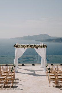 Υπέροχη αψίδα τελετής γάμου με λευκά άνθη, λευκά υφάσματα και θέα το Αιγαίο πέλαγος