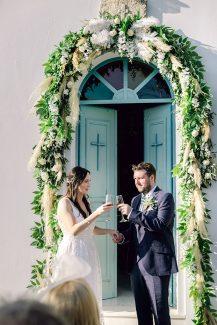 Ρομαντικός στολισμός εισόδου εκκλησίας με πλούσια γιρλάντα πρασινάδας, λευκά τριαντάφυλλα και pampas grass