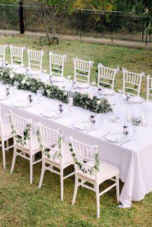 Ρομαντικός στολισμός τραπεζιού δεξίωσης με φύλλα ελιάς και λευκά τριαντάφυλλα