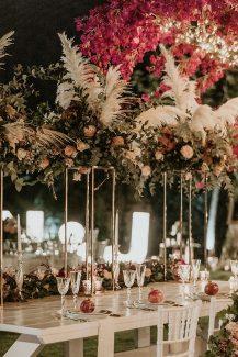 Εντυπωσιακός στολισμός τραπεζιού δεξίωσης με πλούσιες γιρλάντες από άνθη σε φούξια και ροζ τόνους