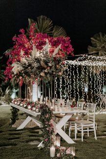 Στολισμός γαμήλιου τραπεζιού με πλούσιες γιρλάντες από άνθη σε φούξια και ροζ τόνους