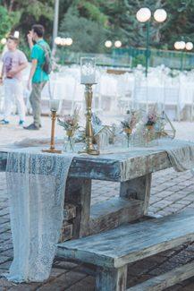 Στολισμός εισόδου εκκλησίας με χρυσούς αμφορείς και λευκό ύφασμα σε ξύλινο black and white τραπέζι