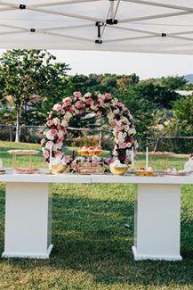 Dessert table σε λευκό χρώμα με κυκλική αψίδα λουλουδιών