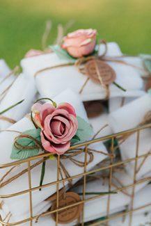 Αναμνηστικά δωράκια – μπομπονιέρες σε λευκό χρώμα που δένουν όμορφα με σχοινάκι διακοσμημένο με τριαντάφυλλο