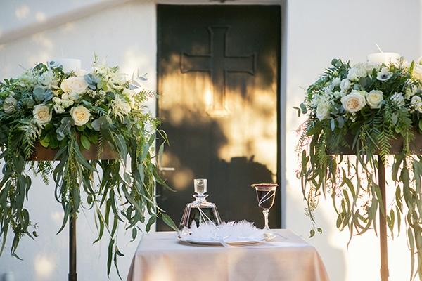 Πλούσιος ανθοστολισμός λαμπάδων εκκλησίας με πρασινάδα και λευκά τριαντάφυλλα και ανεμώνες