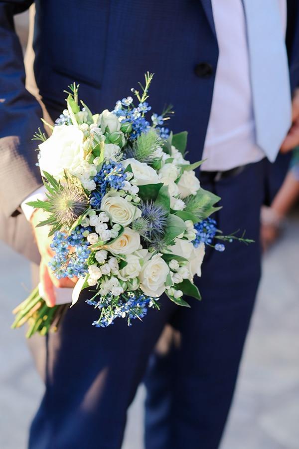 Νυφική ανθοδέσμη με τριαντάφυλλα σε λευκό χρώμα και άλλα ιδιαίτερα μπλε λουλούδια