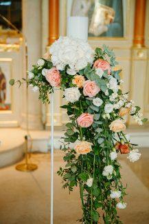 Μοντέρνος στολισμός λαμπάδας σε stand με κρεμαστές συνθέσεις από πρασινάδα και άνθη