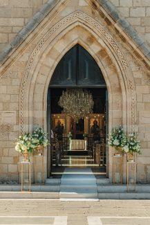 Elegant στολισμός εισόδου εκκλησίας με λουλούδια σε χρυσά stands