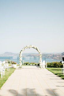 Ρομαντική αψίδα λουλουδιών με λευκά τριαντάφυλλα και θέα το γαλάζιο της θάλασσας