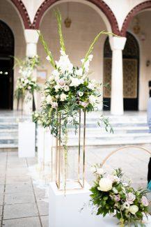 Elegant στολισμός εισόδου εκκλησίας με λευκές γλαδιόλες, τριαντάφυλλα, αμάρανθο, λυσίανθο και πλούσια πρασινάδα ευκαλύπτου