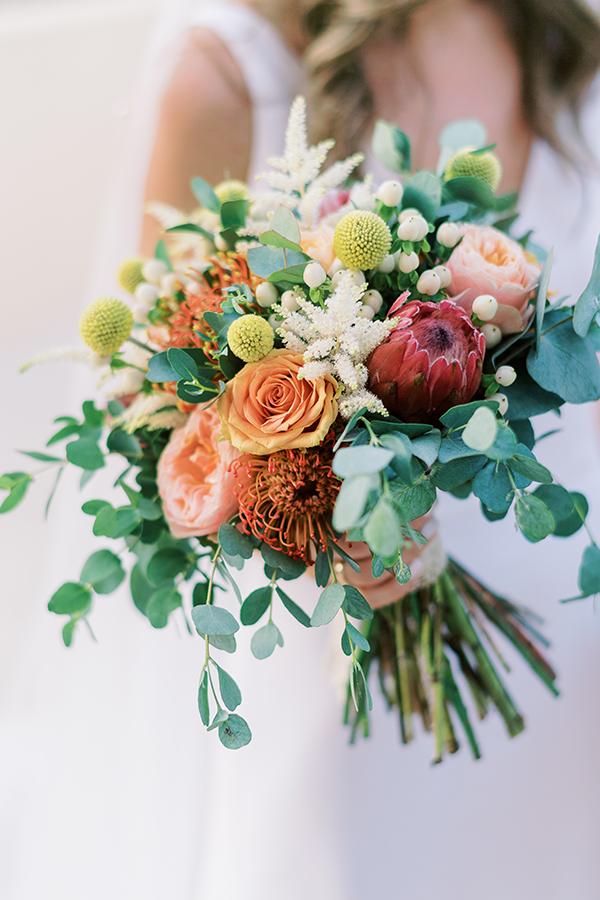 Εντυπωσιακή νυφική ανθοδέσμη με κόκκινη πρωτέα, τριαντάφυλλα και άλλα λουλούδια σε ζεστές αποχρώσεις